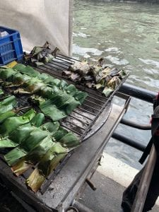 Snack of rice and coconut wrapped in banana leaves on a fire grill